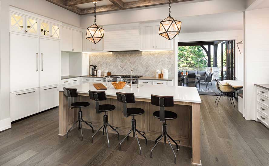 Kitchen Interior with Island, Sink, Cabinets, and Modern apartment interior featuring Johnson Hardwood's British Isles, Species European oak, color Devon in New Luxury Home. Includes elegant pendant light fixtures and wood beam ceiling.