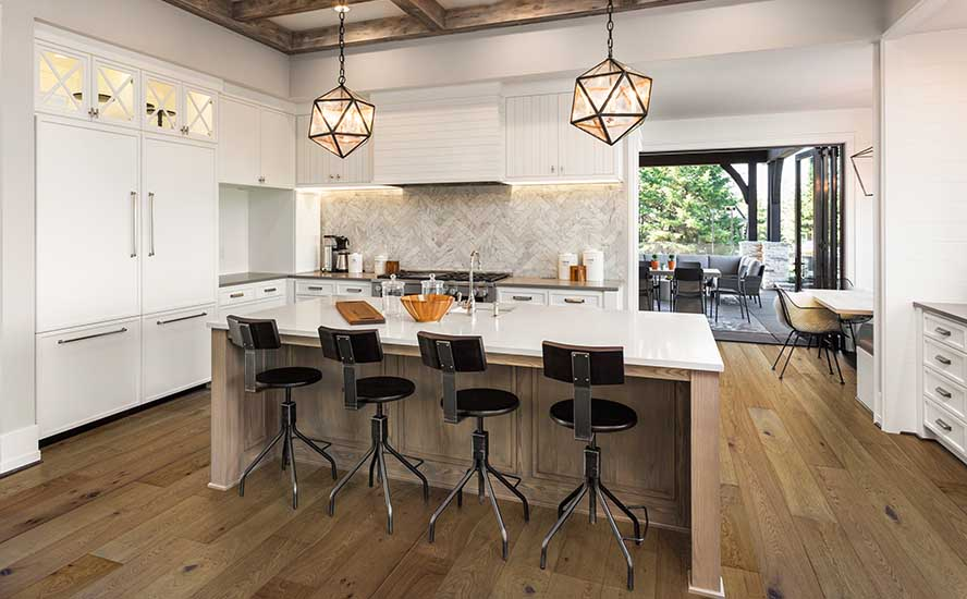 Kitchen Interior with Island, Sink, Cabinets, and Modern apartment interior featuring Johnson Hardwood's British Isles, Species European oak, color Sunderland in New Luxury Home. Includes elegant pendant light fixtures and wood beam ceiling.