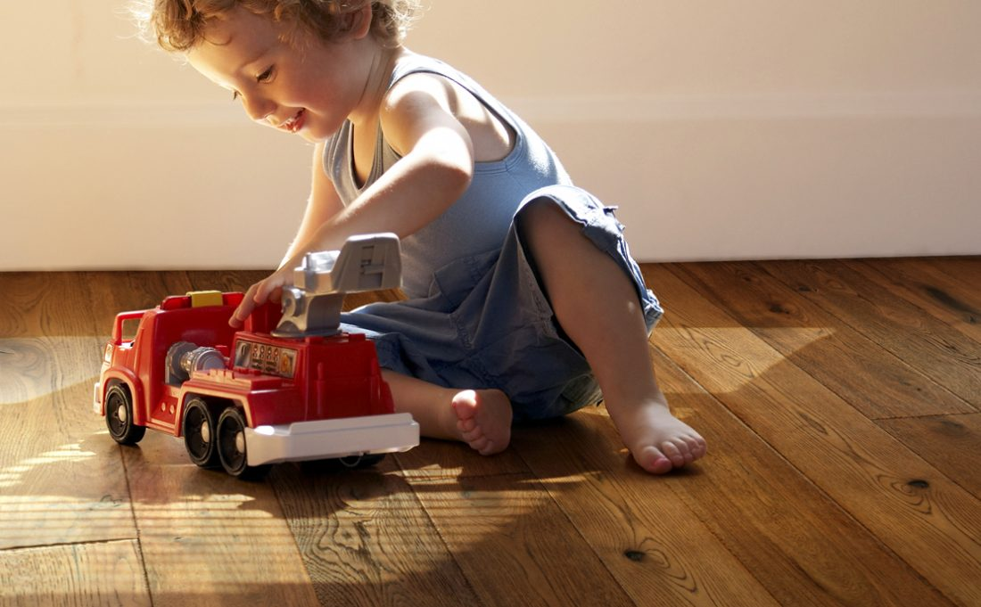 image of child playing on a wood floor.