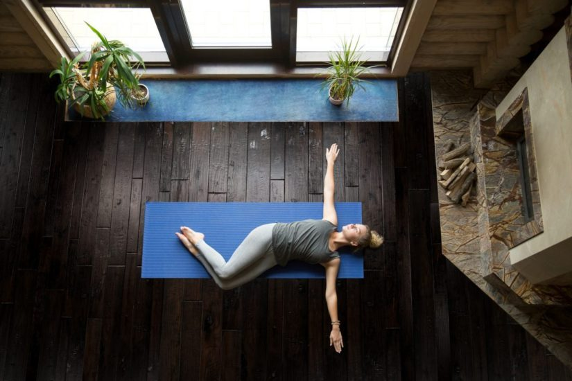 Image showing lady doing yoga on a wood floor.