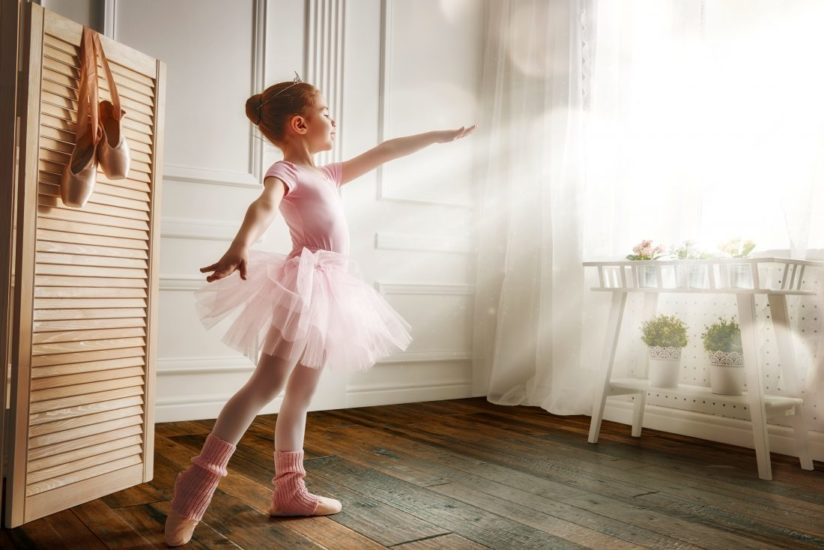 Image showing a young ballerina dancing on a wood floor.