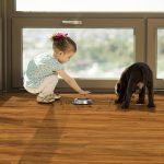 Image of little girl and puppy playing on a hardwood floor.