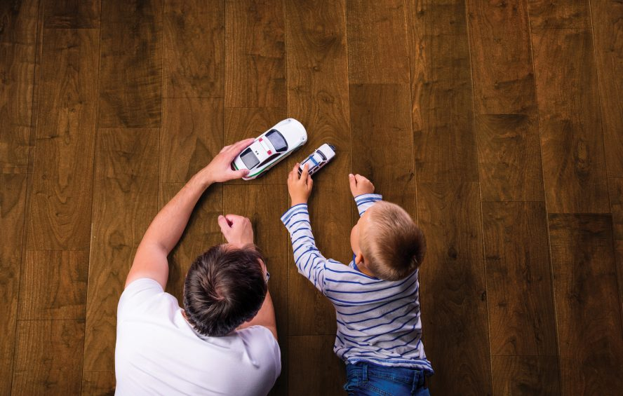 image showing father and son playing on a wood floor.